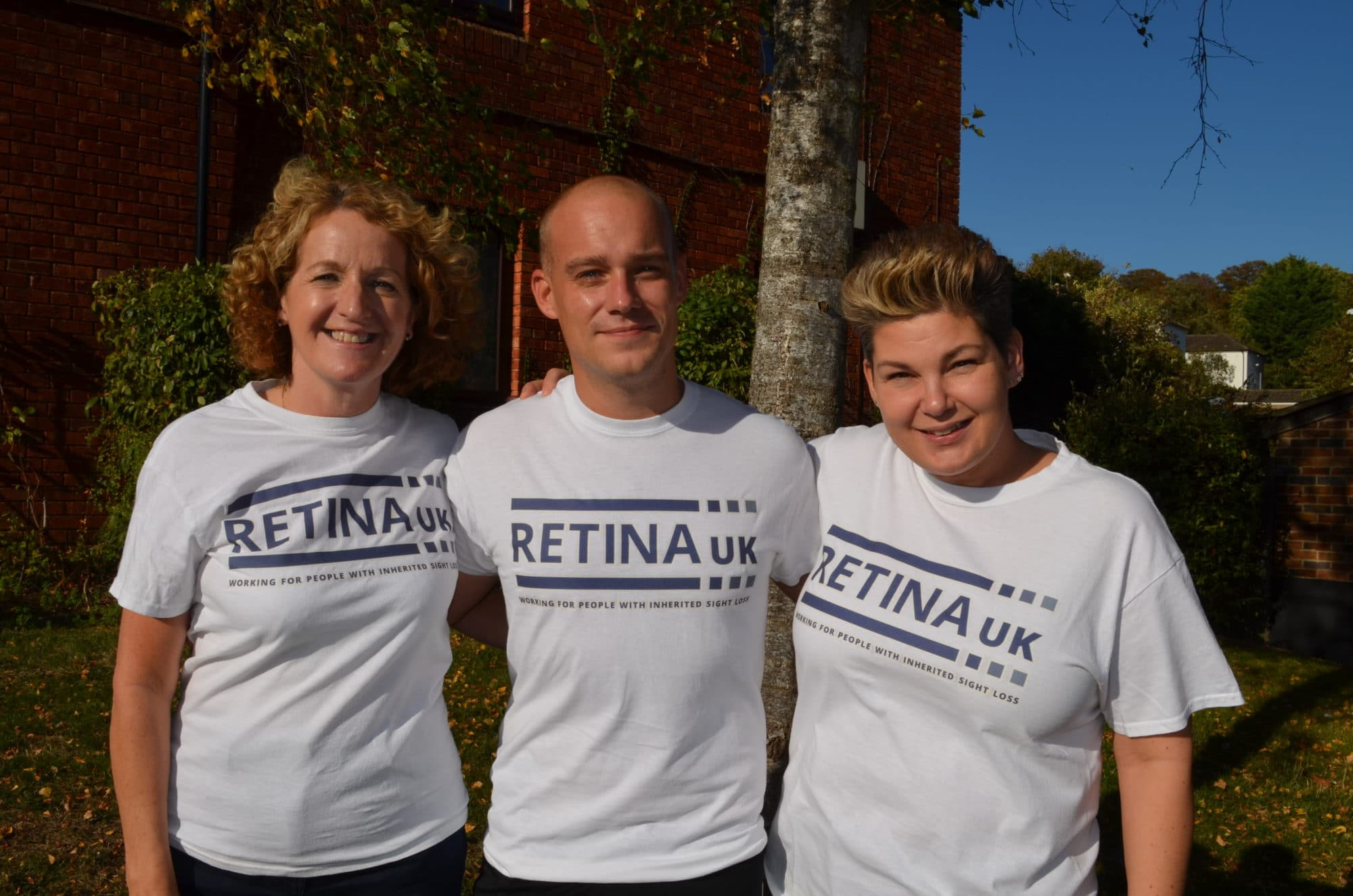 Three people smiling in Retina UK T shirts