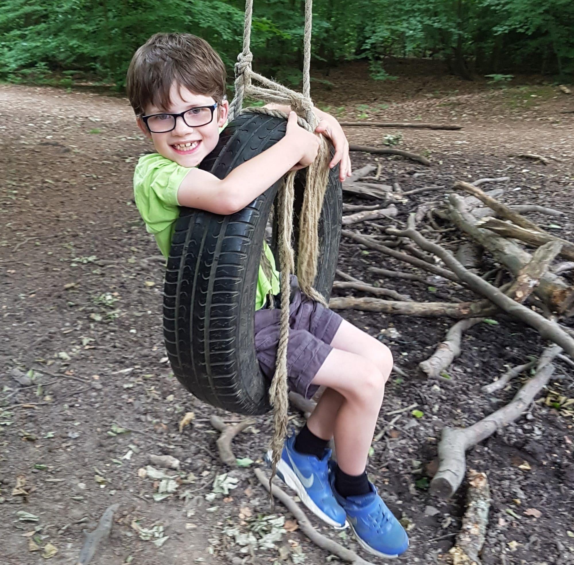Boy smiling on rope swing
