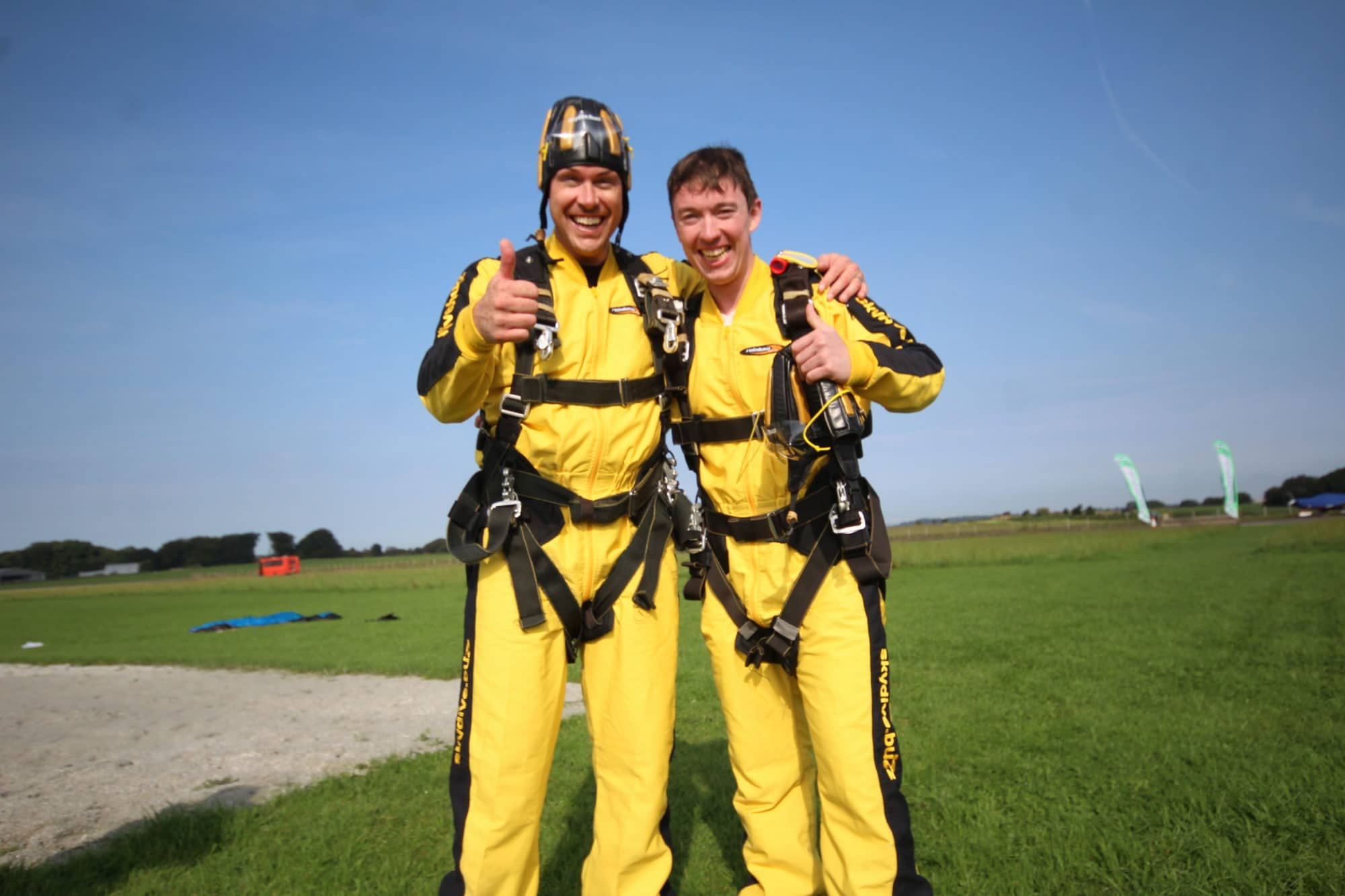 two people giving thumbs up in skydiving suits