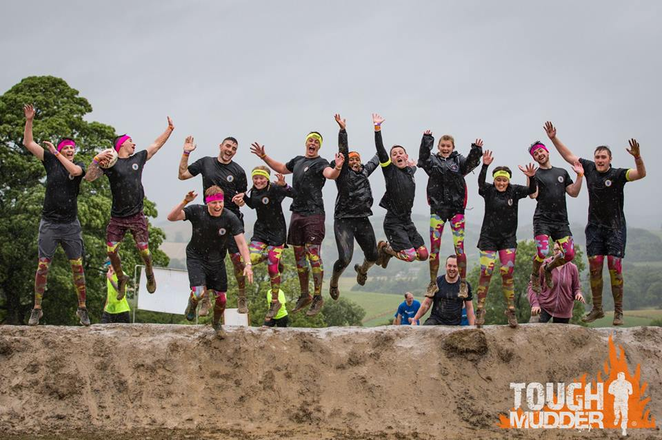 People jumping for joy in mud