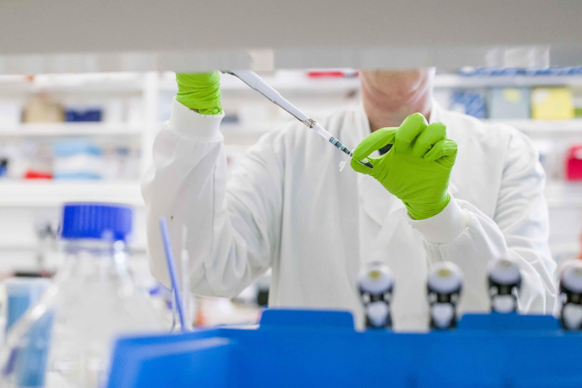 Person in white lab coat using a pipette