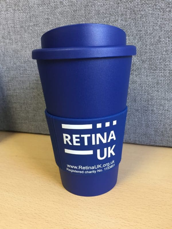 Retina UK insulated coffee cup in navy blue with the cuff showing the Retina UK logo, website url and charity number'. In this image the lid of the cup is on. The image is taken looking directly at the cup.