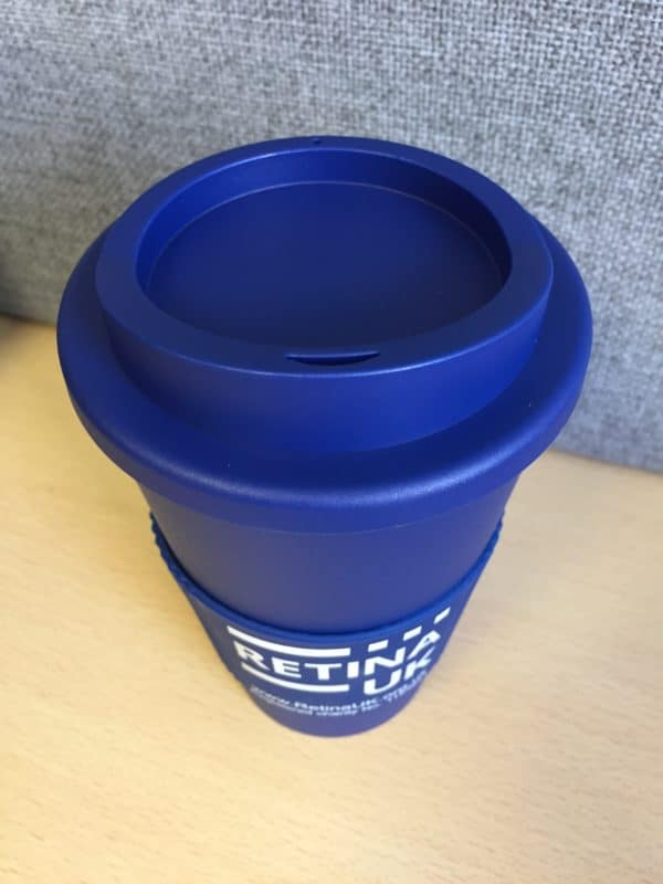 Retina UK insulated coffee cup in navy blue with the cuff showing the Retina UK logo, website url and charity number'. In this image the lid of the cup is on and it is seen from above.
