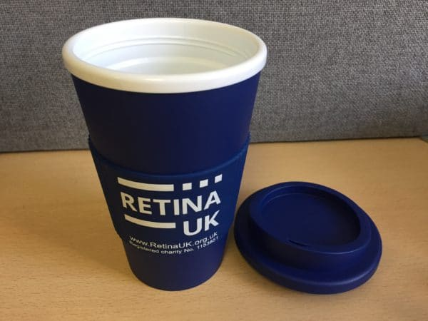 Retina UK insulated coffee cup in navy blue with the cuff showing the Retina UK logo, website url and charity number'. In this image the lid of the cup is off and is placed to the right side of the cup.
