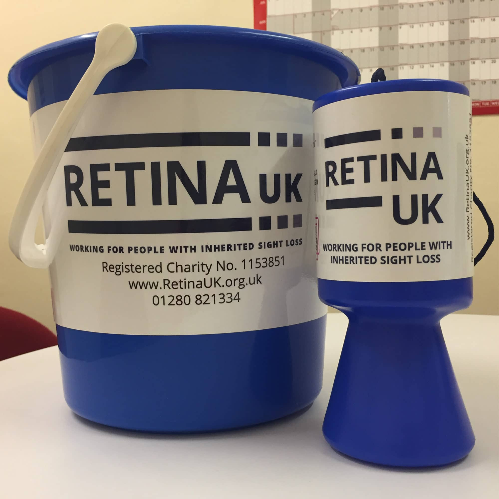 Image shows a blue collection bucket and tin both with white labels showing the Retina UK label in blue text