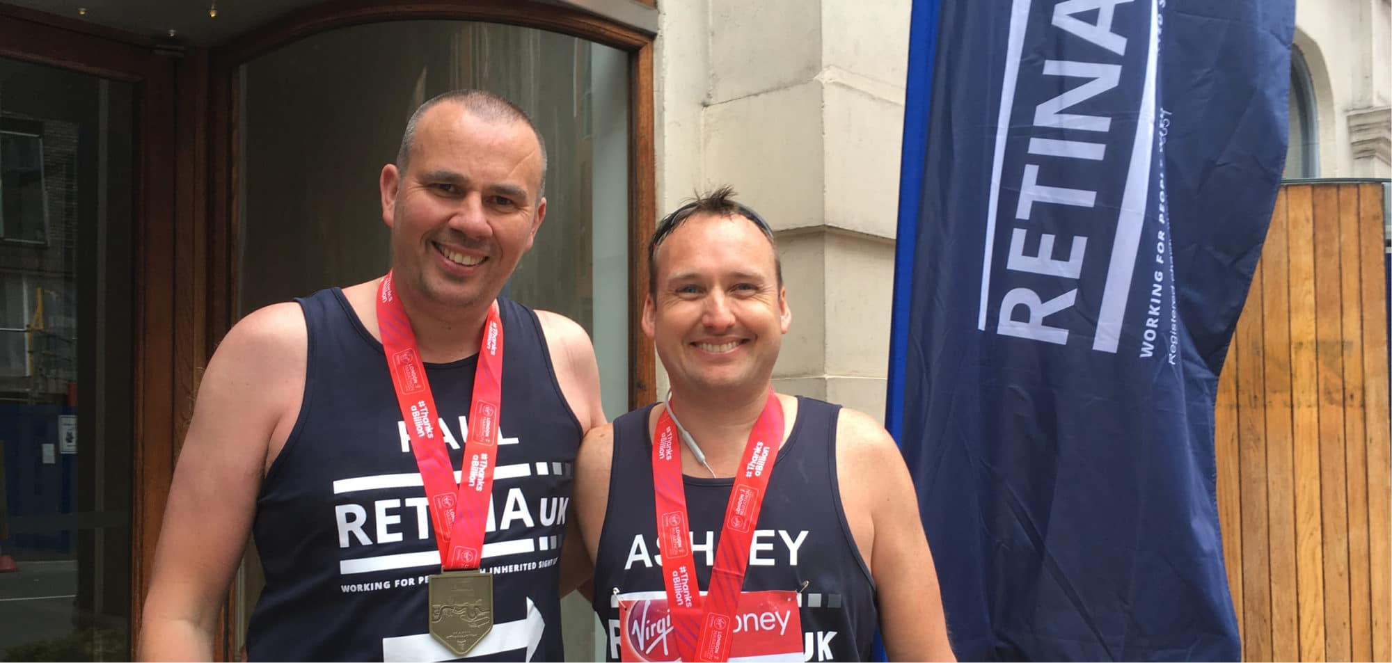 Image shows two Retina UK London Marathon runners - they are standing side by side smiling and wearing their race medals. A blue Retina UK flag is visible behind.