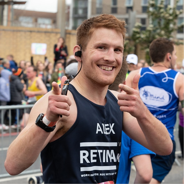 A runner in a Retina UK running vest smiles at the camera in a thumbs up pose
