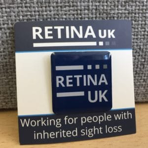 The Retina UK Pin badge mounted on a card with the words 'Working for people with inherited sight loss' printed on the card below the badge