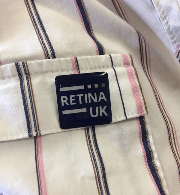 Retina UK pin badge pinned to a shirt (which is white with narrow blue, pink and brown stripes)