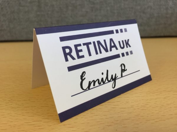 Retina UK A framed place card with the Retina UK logo and a a line to write in the name of the person. In this example the name 'Emily P' has been written in