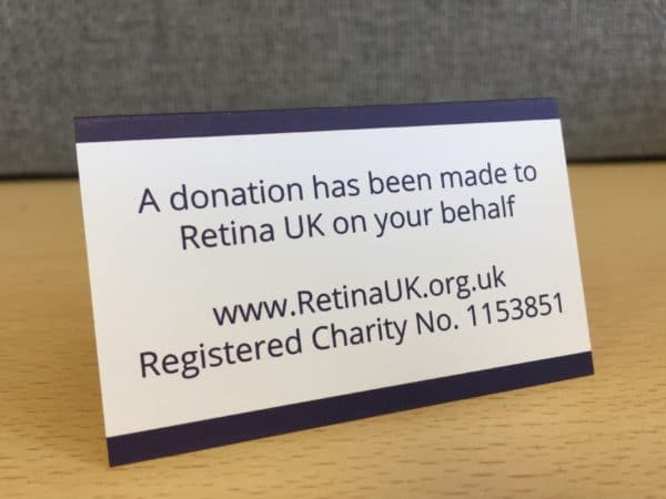 The rear of the Retina UK place card which says 'A donation has been made to Retina UK on your behalf. www.RetinaUK.org.uk, Registered Charity No 1153851'