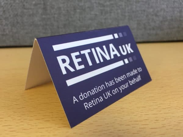 """A tented card viewed from the left side with the Retina UK logo and the words """"A donation has been made to Retina UK on your behalf"""""""