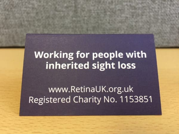 """A tented card viewed straight on with the words """"Working for people with inherited sight loss"""" followed by www.RetinaUK.org.uk, Registered Charity No 1153851"""
