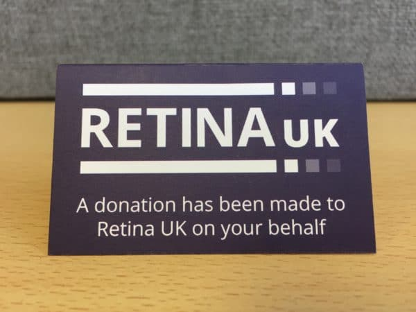 """A tented card viewed straight on with the Retina UK logo and the words """"A donation has been made to Retina UK on your behalf"""""""