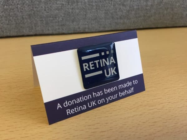 The Retina UK Pin Badget mounted on a A-frame cardboard mount. The words 'A donation has been made to Retina UK on your behalf' printed below it