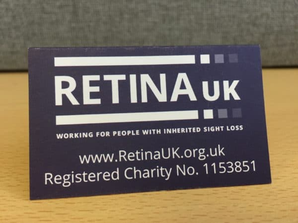 The Retina UK logo with the website url and charity number printed below. This is the rear of the cardboard A frame with the badge mounted on the other side