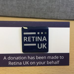 The Retina UK Pin badge mounted on card with the words 'A donation has been made to Retina UK on your behalf' printed underneath
