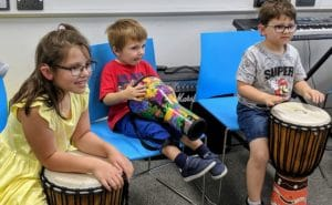 Three children playing bongo drums whilst sitting on chairs
