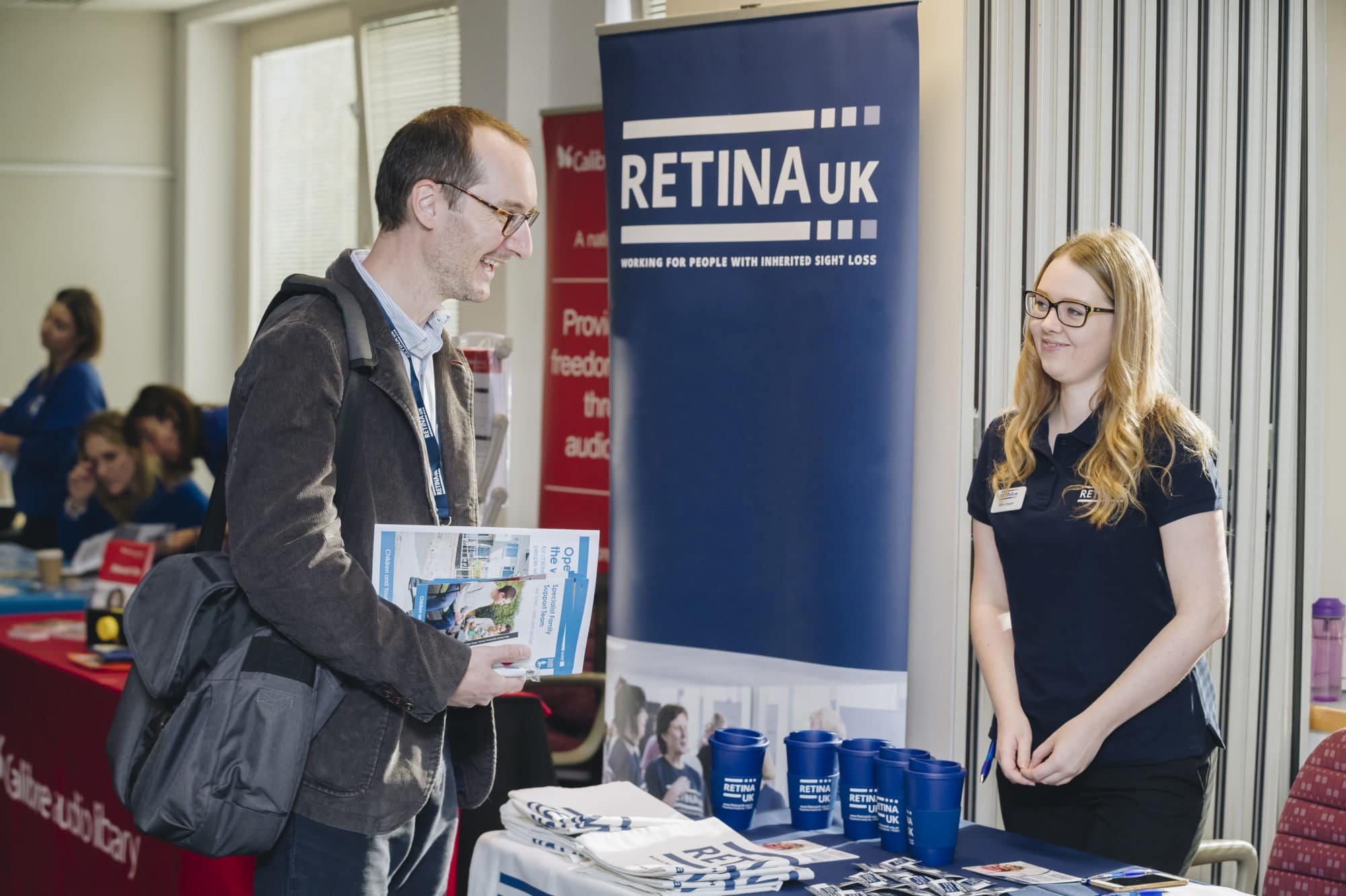 A man speaking to a Retina UK member of staff