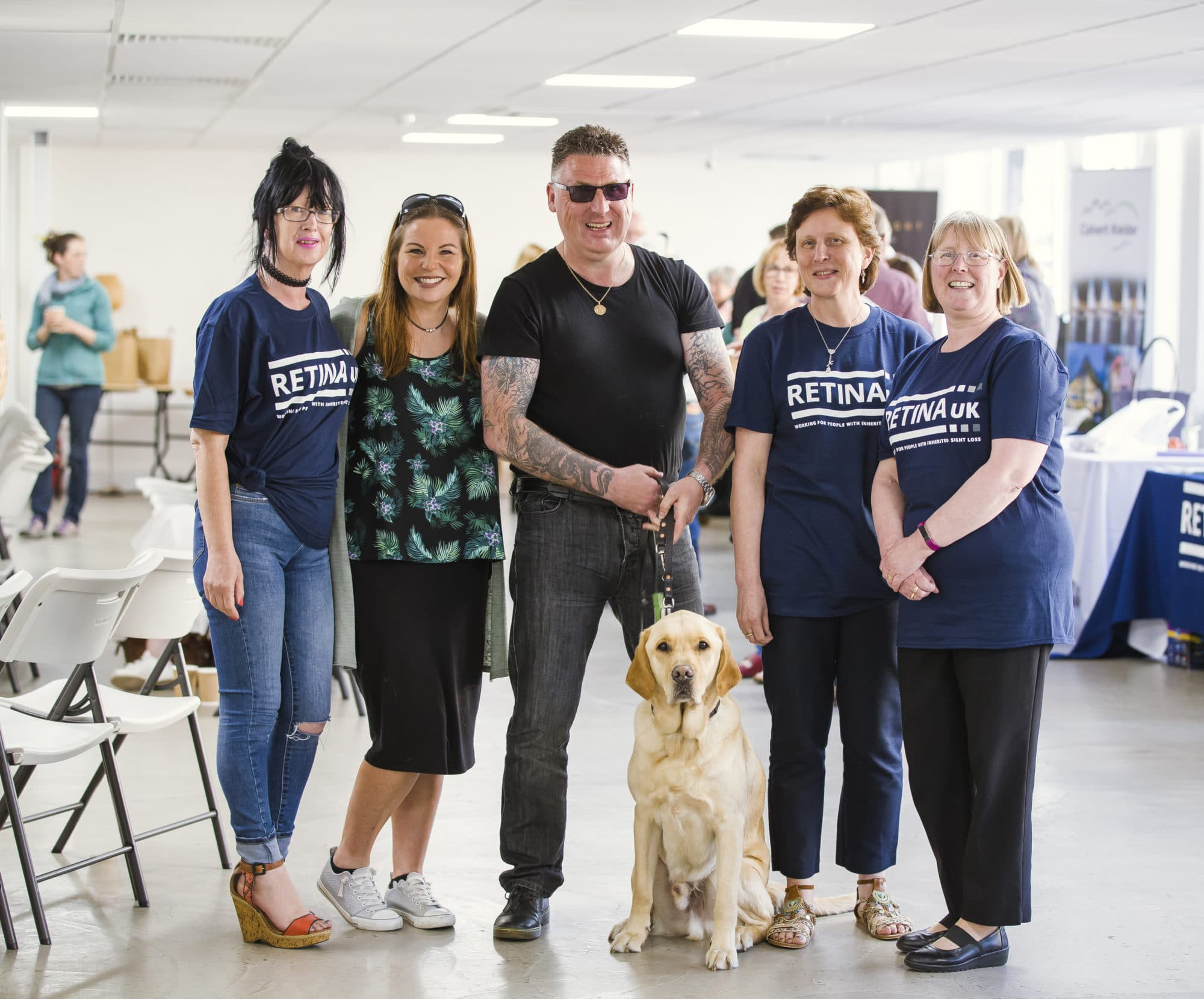 Three Retina UK volunteers with a man, woman and guide dog
