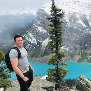 James Clubb standing next to a tree overlooking a turquoise colour lake