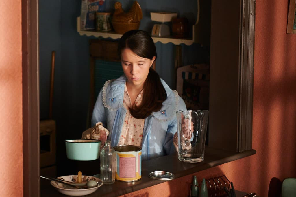 The character Marion, standing in her kitchen
