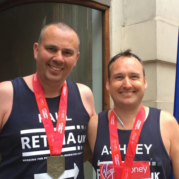 Image shows two male Retina UK runners standing smiling. Both are wearing blue Retina UK running vests and their red London Marathon medals