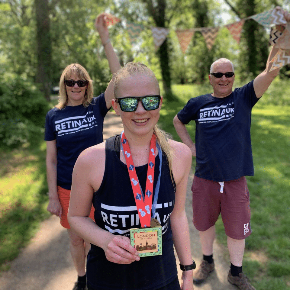 Image shows a supporter in a Retina UK running vest holding a medal after completing a virtual race. Two family members are stood in the distance holding bunting.