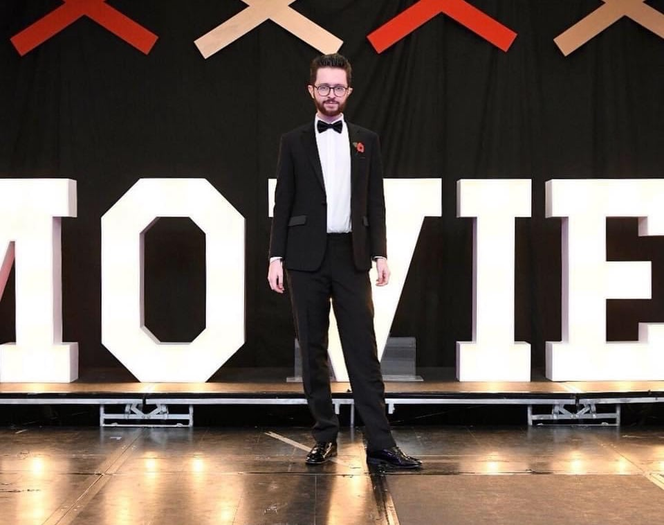 James Clarke wearing a tuxedo standing in front of enormous white letters spelling out the word 'movie'