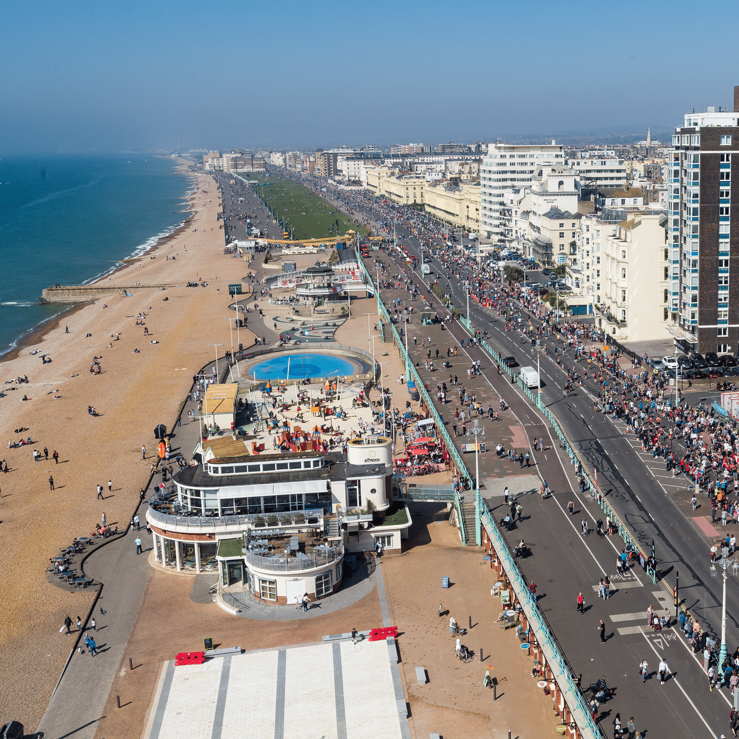 Image shows thousands of runners on Brighton's seafront road.
