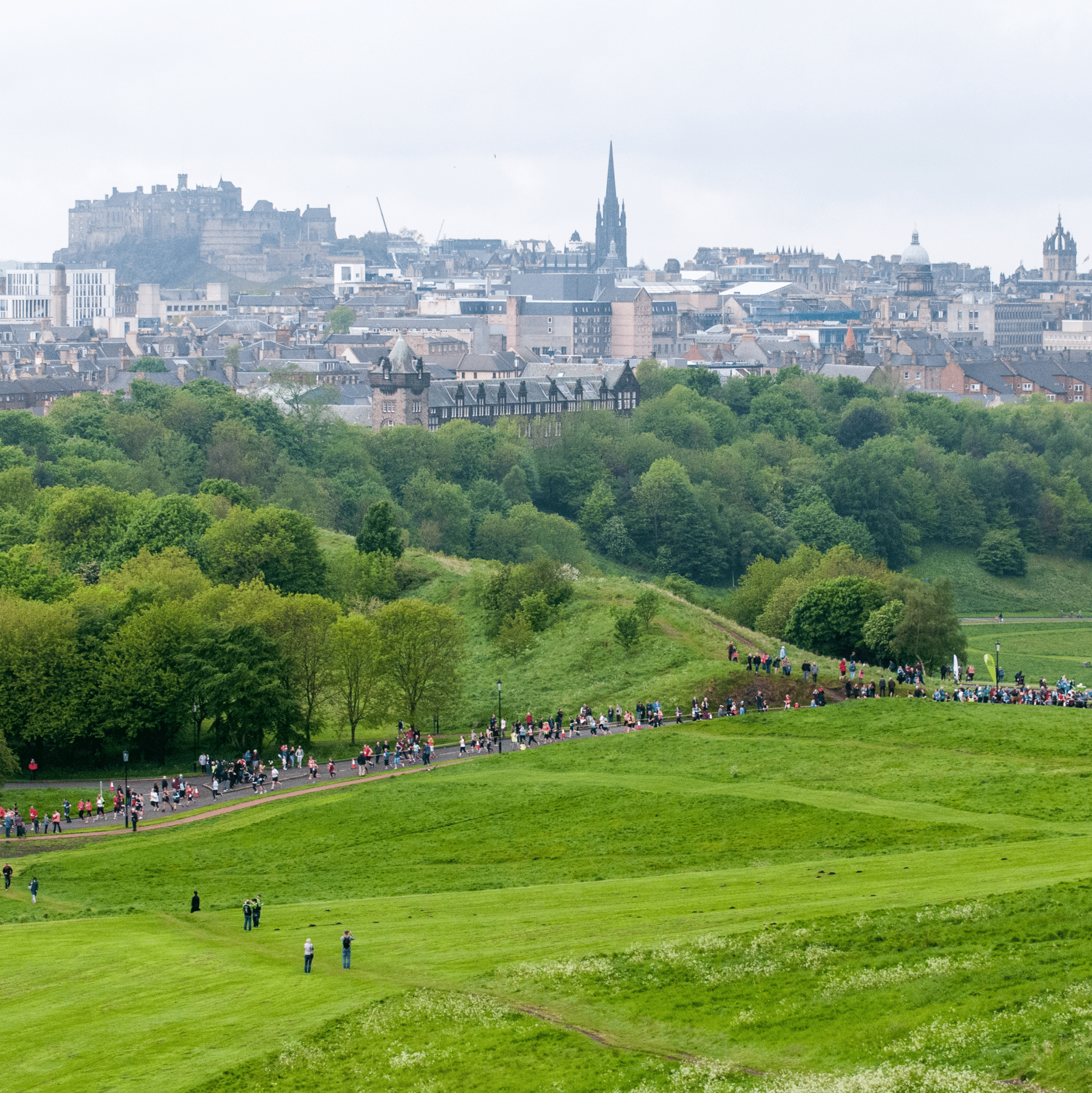 Image shows hundreds of runners running on the paths in holyrood park with Edinburgh Castle and Scott monument in the distance