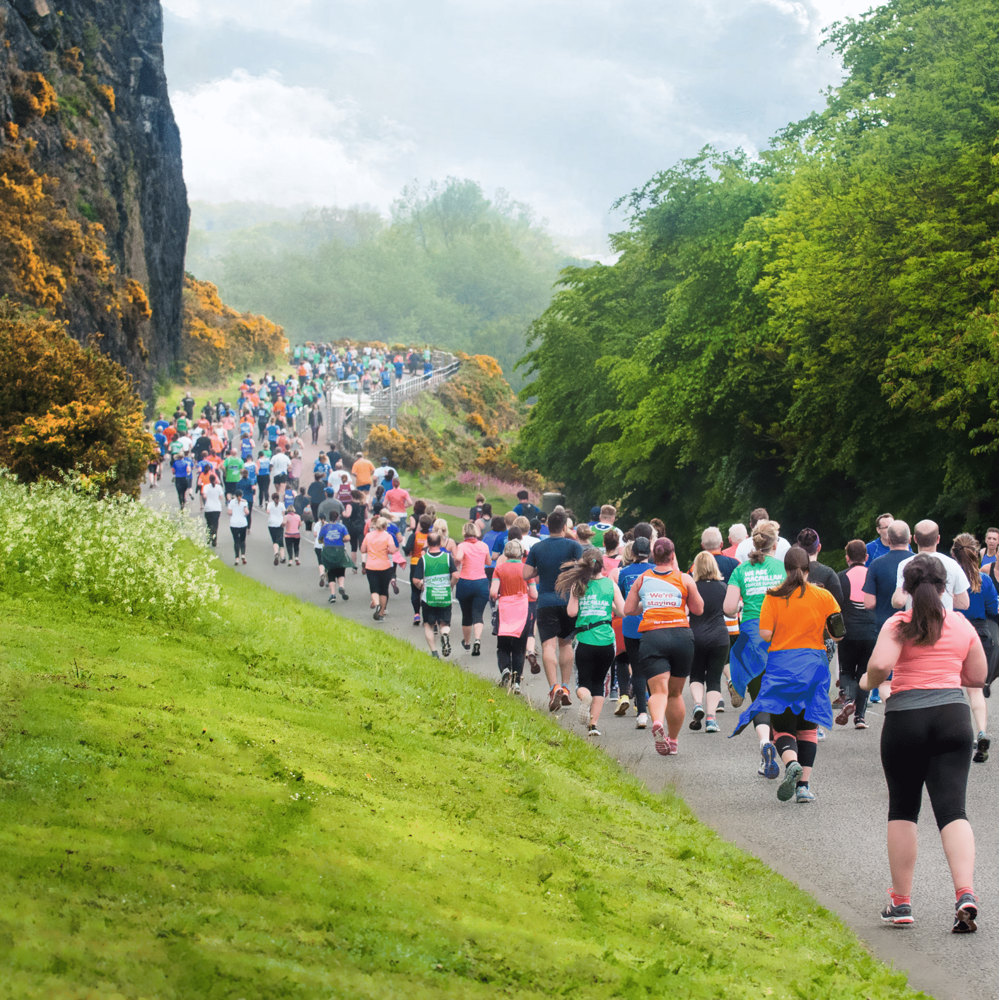 Image shows hundreds of runners running down a path in Holyrood Park. Yellow flowering gorse contrasts against the dark rock cliffs.