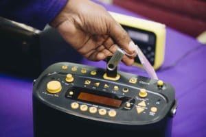 A black radio with yellow buttons and a hand inserting a memory stick into it