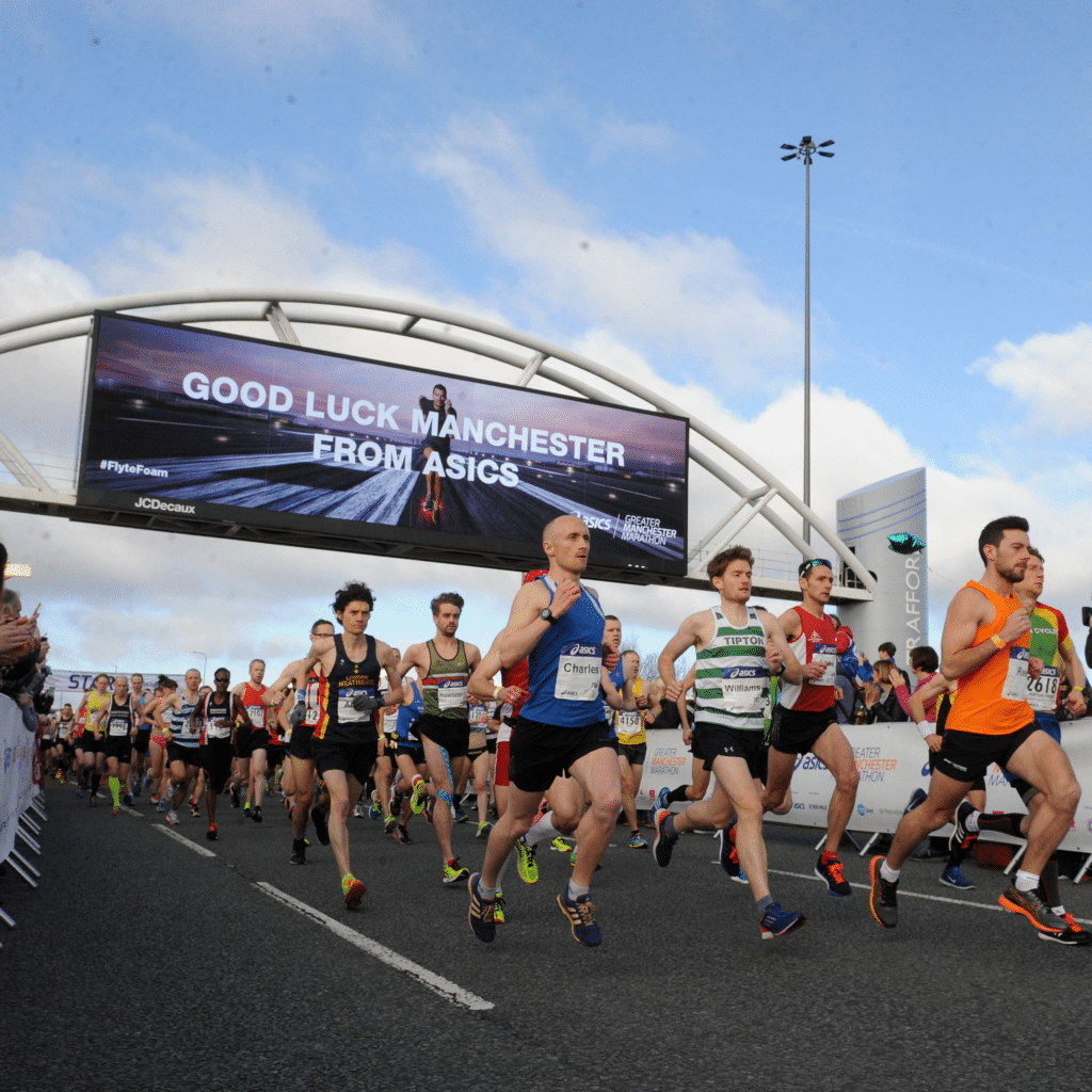 Image shows runners running down a road with a digital sign above that reads 'Good luck Manchester'