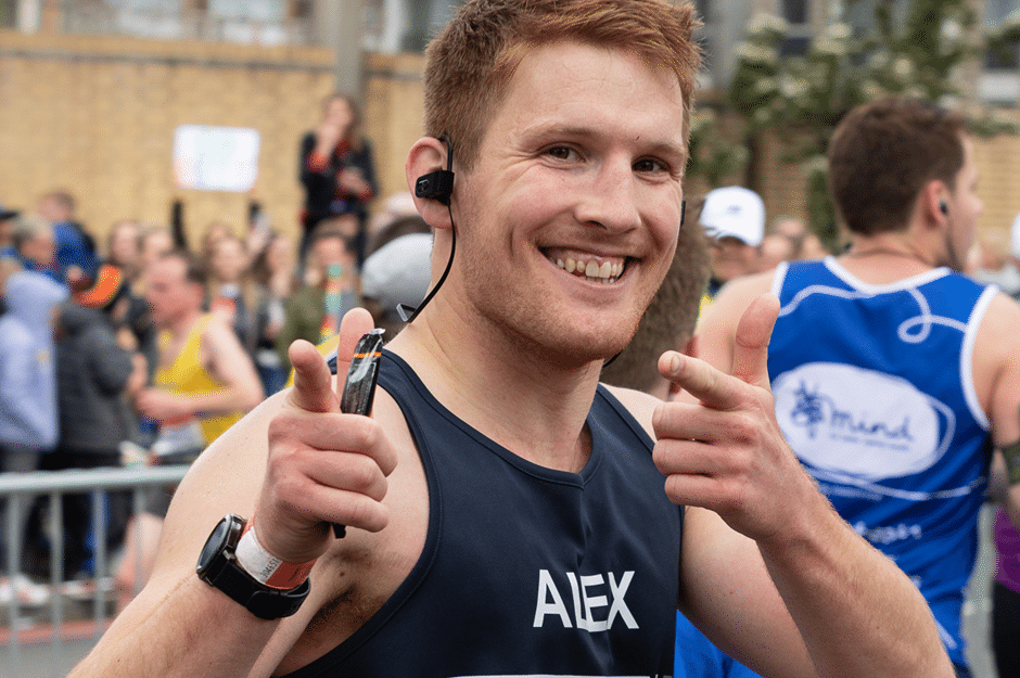 A runner is shown in a Retina UK runnning vest posing with a thumbs up