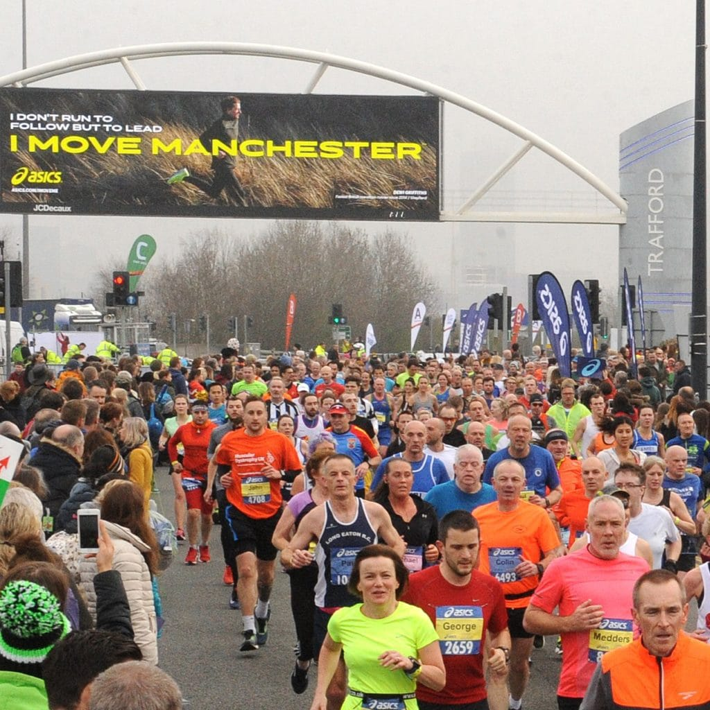 Image shows runners running down a road with a sign above that reads 'I Move Manchester'