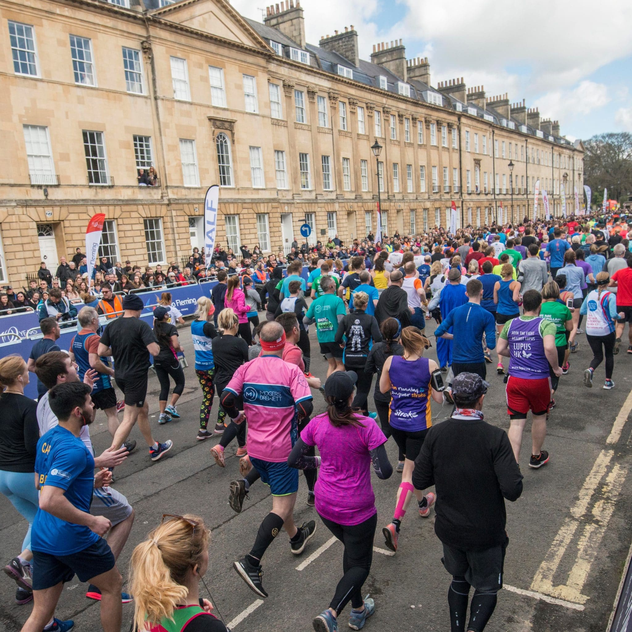 Image shows a crowd of runners running along a road lined with Bath's historic stone buildings