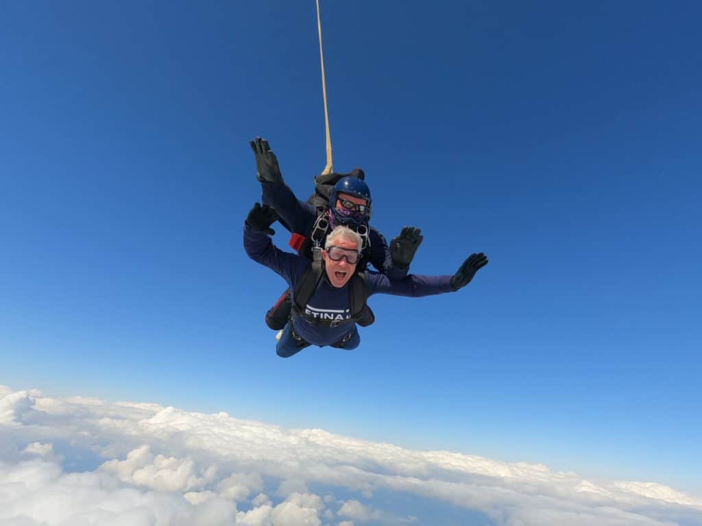 Image shows two people in a tandem skydive - blue sky and clouds are visible.