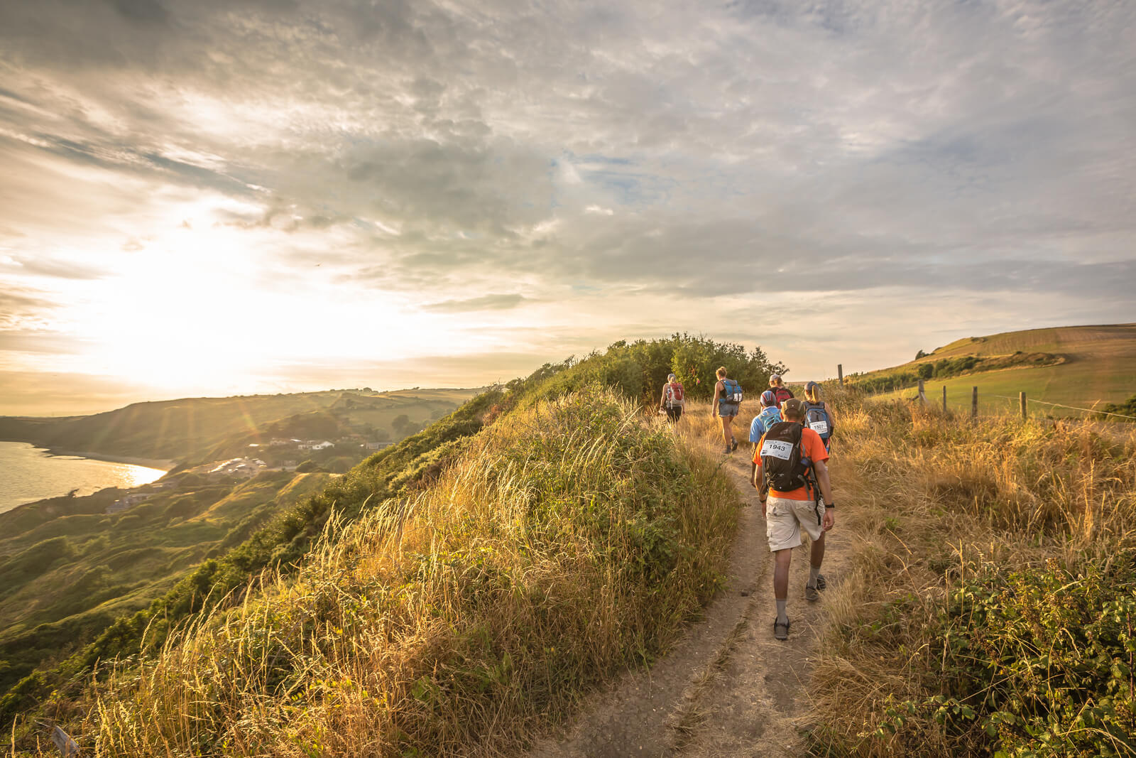 Image shows six walkers walking along a hillside path with a sunset in the background.