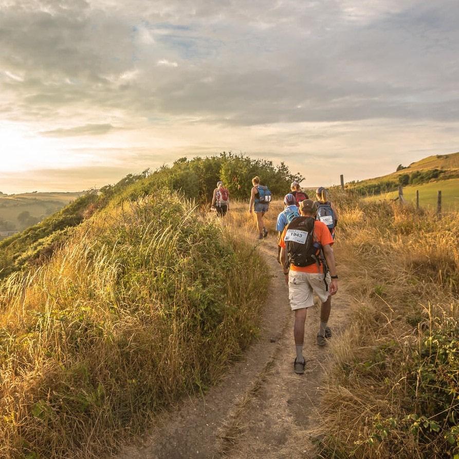 Image shows six walkers walking along a hillside path.