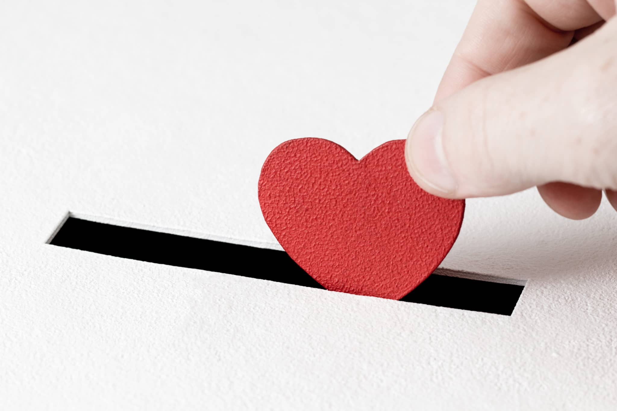 A small red heart being posted into a slot