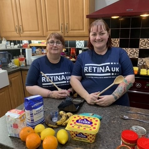 image shows two supporters stood next to each other in a kitchen smiling. Both are wearing blue Retina UK t-shirts and are holding wooden mixing spoons