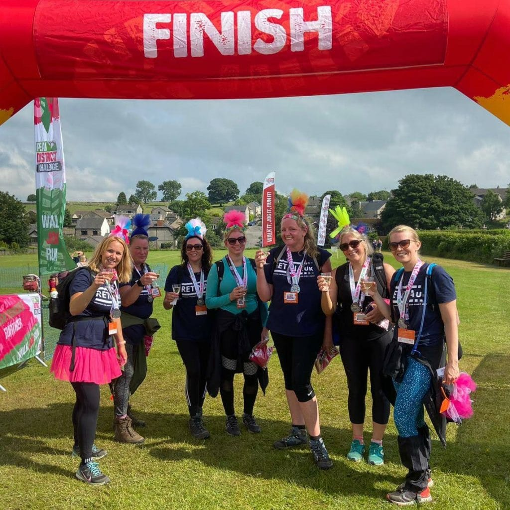 Image shows a group of 7 walkers at the finish line. They are each smiling, wearing a blue Retina UK t-shirt and are holding a glass of fizz.
