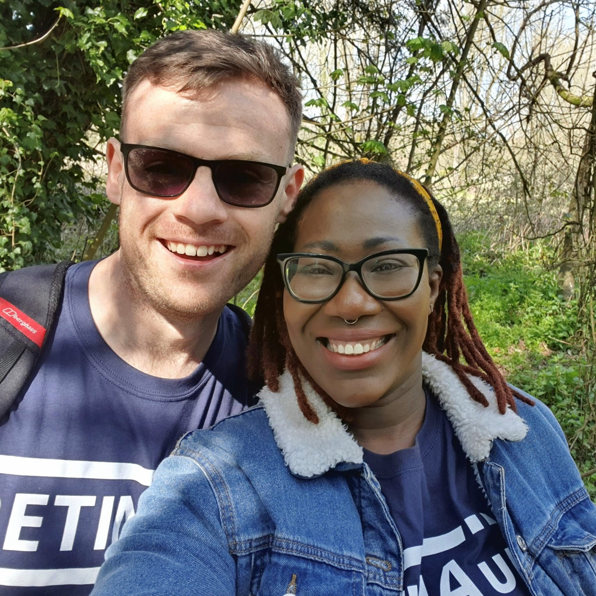 Image shows two supporters stood next to each other smiling in front of a hedgerow. Both are wearing blue Retina UK t-shirts.